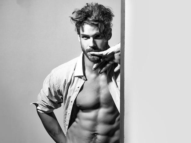 Nachdenklicher gutaussehender mann im aufgeknöpften hemd zeigt auf sechs packungen und bauchmuskeln am muskeltorso.