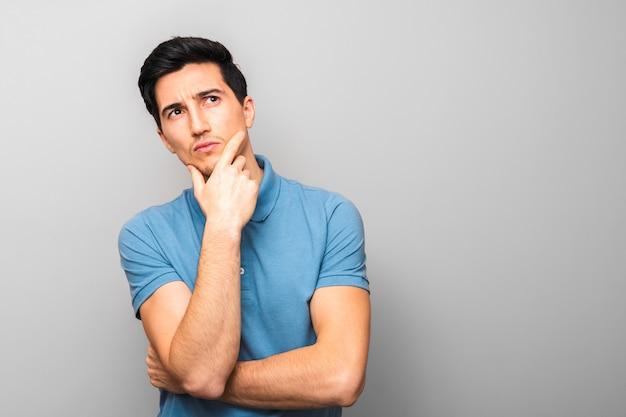 Nachdenklicher gutaussehender mann im blauen hemd mit hand auf seinem kinn, das oben gegen grauen hintergrund mit kopienraum sucht