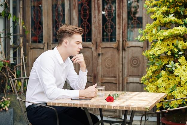 Nachdenklicher hübscher junger mann, der am tisch im straßencafé sitzt und rote rose für seine freundin betrachtet
