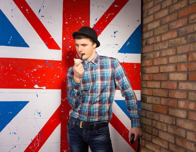 Nachdenklicher hübscher junger mann in lässigem outfit rauchen mit tabakpfeife vor riesigem uk-flaggen-druck.