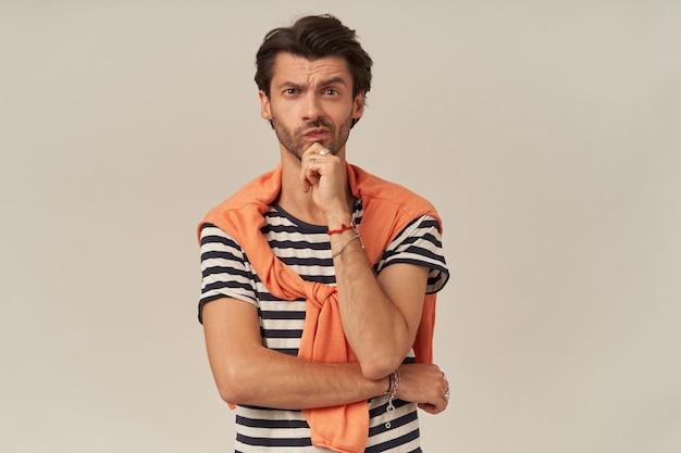 Nachdenklicher hübscher junger mann mit borsten im gestreiften t-shirt und pullover auf den schultern hält hände gefaltet, berührt sein kinn und denkt nach