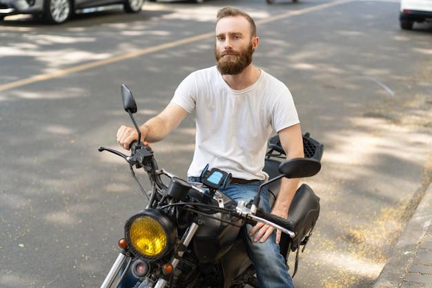 Nachdenklicher hübscher radfahrer, der mit motorrad aufwirft