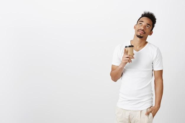 Nachdenklicher hübscher schwarzer mann im lässigen t-shirt, der verträumt aussieht und kaffee trinkt