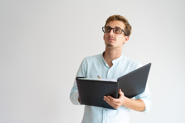 Nachdenklicher intelligenter experte, der herum schaut und anmerkungen macht.