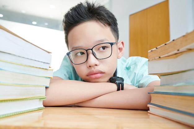Nachdenklicher jugendlicher junge in gläsern, der große stapel bücher auf seinem schreibtisch betrachtet
