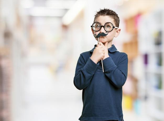 Nachdenklicher junge mit brille und schnurrbart