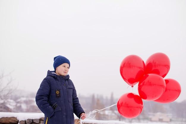 Nachdenklicher junge mit luftballons