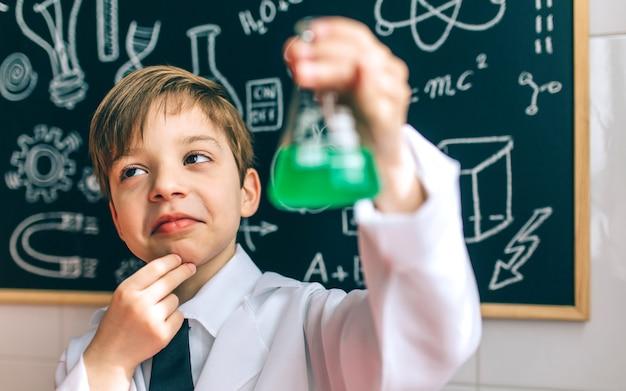 Nachdenklicher junge verkleidet als chemiker mit flasche vor einer tafel mit zeichnungen