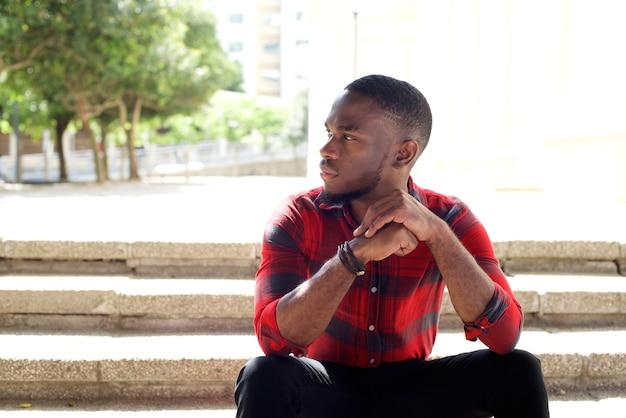 Nachdenklicher junger afrikanischer mann, der auf schritten sitzt