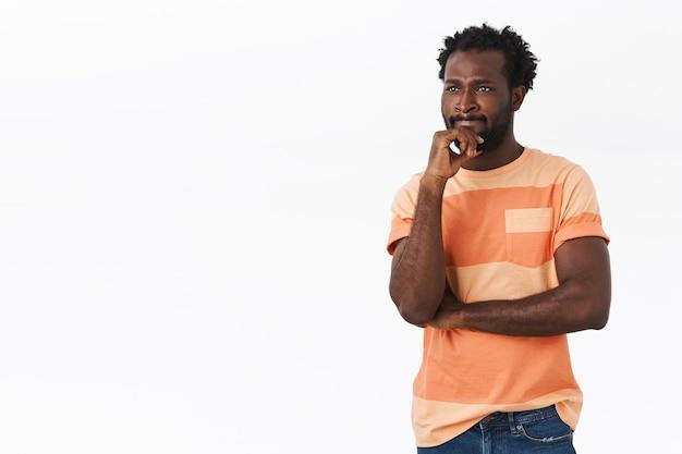 Nachdenklicher junger afroamerikaner, der beunruhigt aussieht
