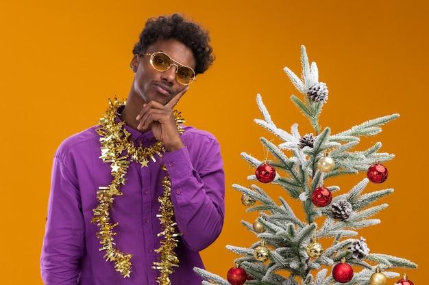 Nachdenklicher junger afroamerikanischer mann, der brille mit lametta-girlande um den hals trägt, der nahe verziertem weihnachtsbaum auf orange hintergrund steht