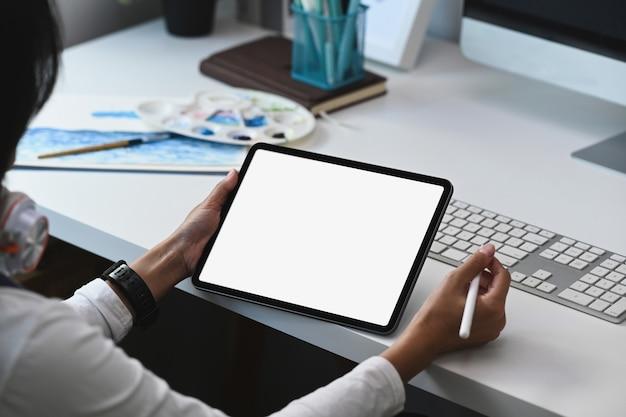 Nachdenklicher junger attraktiver designer, der farbmuster analysiert und computertablett am kreativen arbeitsplatz verwendet.
