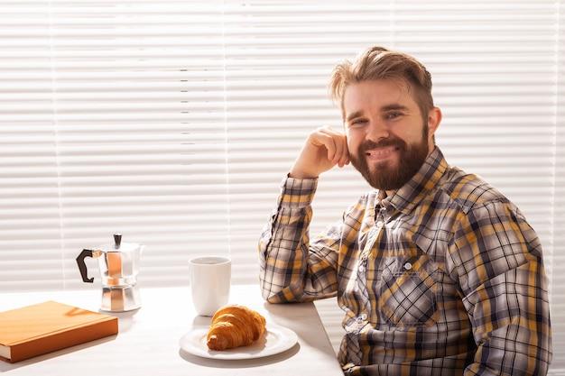 Nachdenklicher junger bärtiger männlicher geschäftsmann, der tasse kaffee auf hintergrund des blinds-konzepts von trinkt