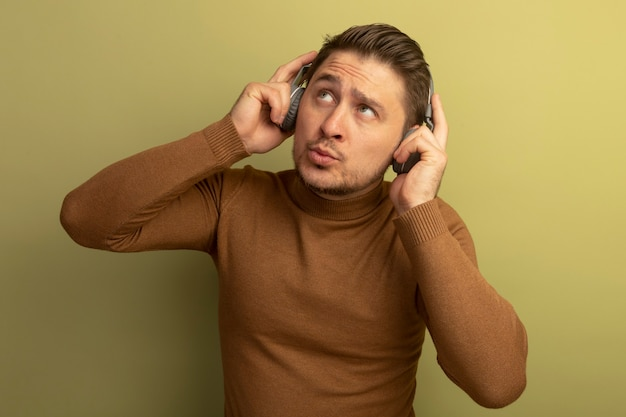 Nachdenklicher junger blonder gutaussehender mann, der kopfhörer trägt und greift, der isoliert auf olivgrüner wand nach oben schaut
