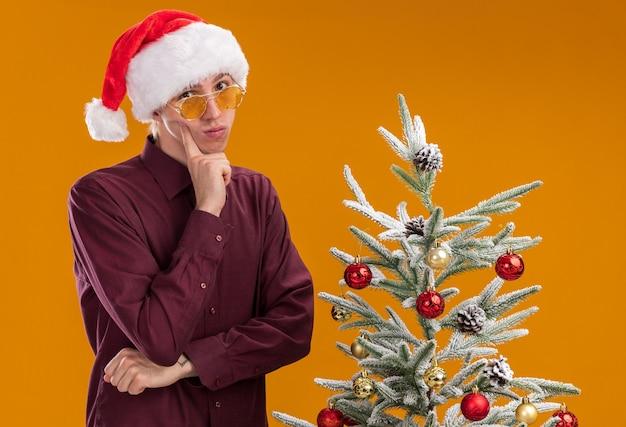 Nachdenklicher junger blonder mann, der weihnachtsmütze und gläser trägt, die nahe geschmücktem weihnachtsbaum auf orange hintergrund stehen