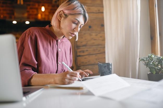 Nachdenklicher junger büroangestellter, der unterlagen überprüft, die von zu hause aus arbeiten. ernsthafte frau, die bericht liest, am tisch mit laptop sitzt.