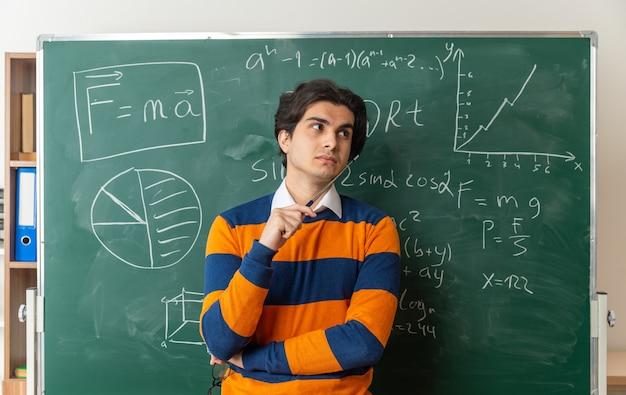 Nachdenklicher junger geometrielehrer, der im klassenzimmer vor der tafel steht und auf die seite schaut, die den zeiger hält