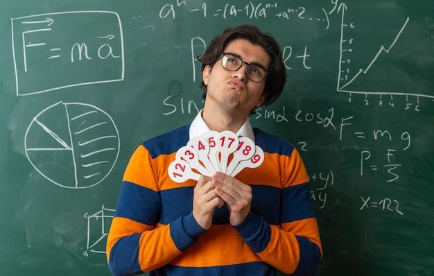 Nachdenklicher junger geometrielehrer mit brille, der im klassenzimmer vor der tafel steht und zahlenfans hält, die mit geschürzten lippen aufblicken
