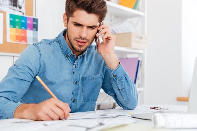 Nachdenklicher junger geschäftsmann, der mit dokumenten arbeitet, während er im büro telefoniert