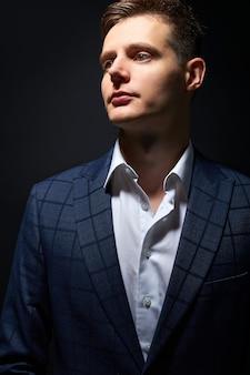 Nachdenklicher junger geschäftsmann im klassischen schwarzen anzug