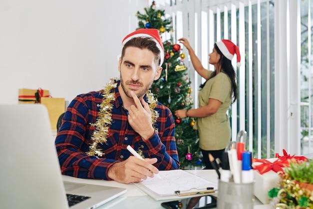 Nachdenklicher junger geschäftsmann in der weihnachtsmannmütze, der an jahresbericht arbeitet, wenn sein kollege weihnachtsbaum im büro verziert