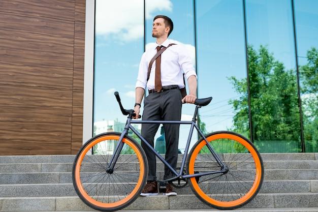 Nachdenklicher junger geschäftsmann mit dem fahrrad, das auf treppen draußen auf hintergrund der fenster des zeitgenössischen bürozentrums steht