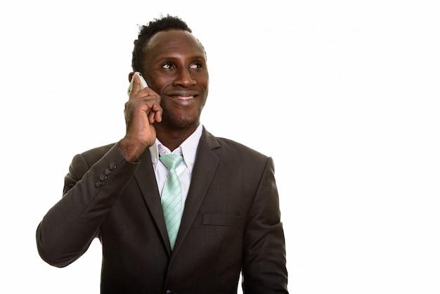 Nachdenklicher junger glücklicher afrikanischer geschäftsmann, der beim sprechen lächelt