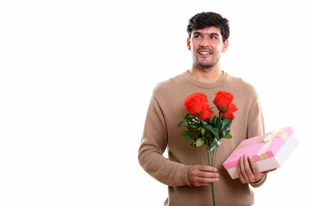 Nachdenklicher junger glücklicher persischer mann, der lächelt, während er roten ros hält
