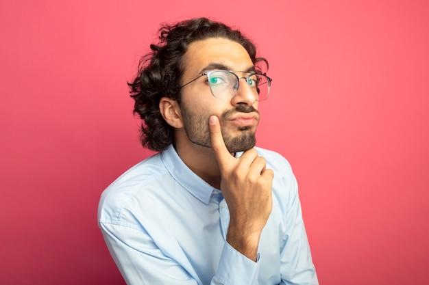 Nachdenklicher junger gutaussehender mann, der eine brille trägt, die das vordere berührende kinn lokalisiert auf rosa wand betrachtet