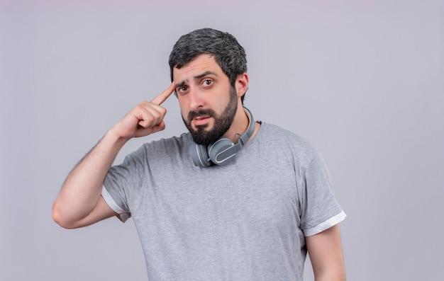 Nachdenklicher junger gutaussehender mann, der kopfhörer am hals trägt und finger auf schläfe lokalisiert auf weißer wand setzt