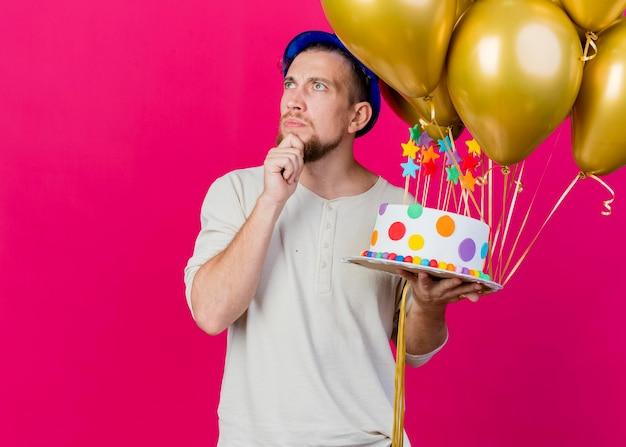 Nachdenklicher junger gutaussehender slawischer party-typ, der partyhut hält, der luftballons und geburtstagstorte mit sternen berührt, die kinn berühren, das seite lokalisiert auf rosa wand mit kopienraum betrachtet