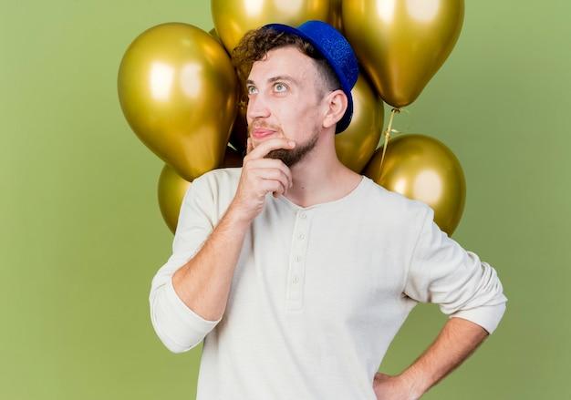 Nachdenklicher junger gutaussehender slawischer party-typ, der partyhut trägt, der vor luftballons steht und das berührende kinn betrachtet, das hand auf taille hält, die auf olivgrüner wand lokalisiert wird