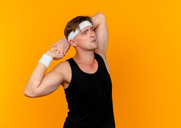 Nachdenklicher junger gutaussehender sportlicher mann, der stirnband und armbänder trägt und hände mit gekreuzten fingern hinter dem kopf hält, der seite betrachtet, die auf orange wand lokalisiert ist