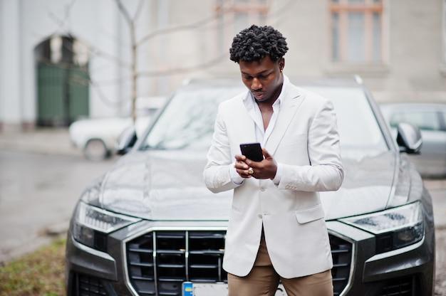 Nachdenklicher junger hübscher afroamerikanerherr in der abendgarderobe. schwarzer stilvoller modellmann in der weißen jacke mit handy an händen gegen geschäftsauto.