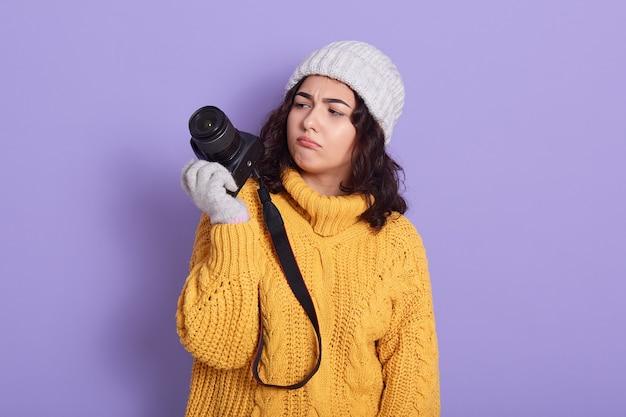 Nachdenklicher junger hübscher europäischer mädchenfotograf, der moderne kamera verwendet