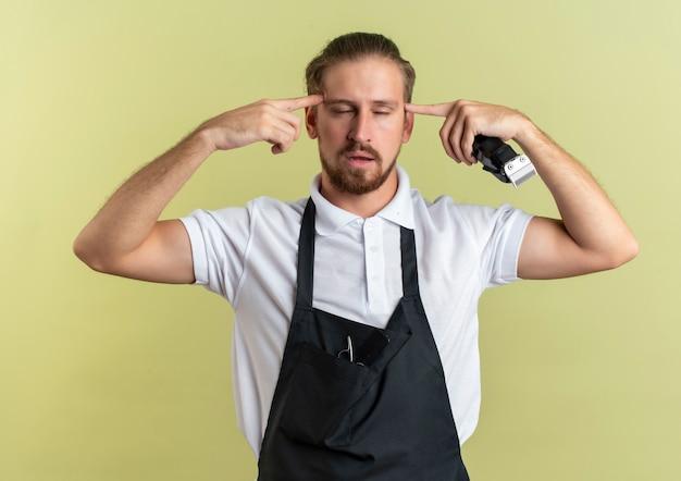 Nachdenklicher junger hübscher friseur, der haarschneidemaschinen hält, die finger auf schläfen mit geschlossenen augen setzen, die auf olivgrüner wand lokalisiert werden