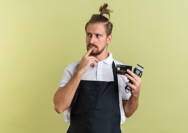 Nachdenklicher junger hübscher friseur, der kreditkarte und haarschneidemaschine hält, die finger auf lippe setzen, die seite lokalisiert auf olivgrüner wand betrachtet