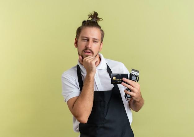 Nachdenklicher junger hübscher friseur, der kreditkarte und haarschneidemaschinen hält, die seite lokalisiert auf olivgrüner wand betrachten