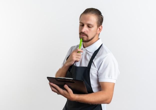 Nachdenklicher junger hübscher friseur, der uniform hält und klemmbrett betrachtet und sein kinn mit stift berührt auf weißer wand berührt