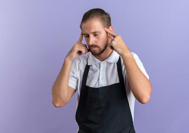 Nachdenklicher junger hübscher friseur, der uniform trägt, die finger auf schläfe mit geschlossenen augen lokalisiert auf lila wand setzt