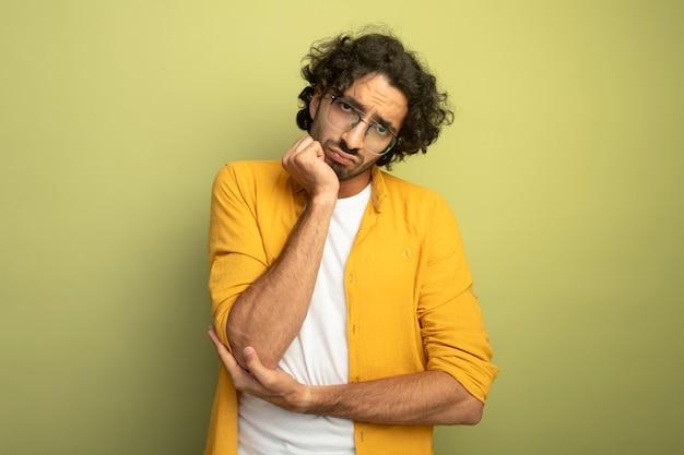 Nachdenklicher junger hübscher kaukasischer mann, der brillen trägt, die kamera betrachten hand auf kinn lokalisiert auf olivgrünem hintergrund mit kopienraum setzen