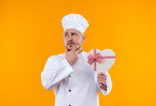 Nachdenklicher junger hübscher koch in der kochuniform, die herzförmige geschenkbox mit hand auf kinn hält, die seite lokalisiert auf orange raum betrachtet