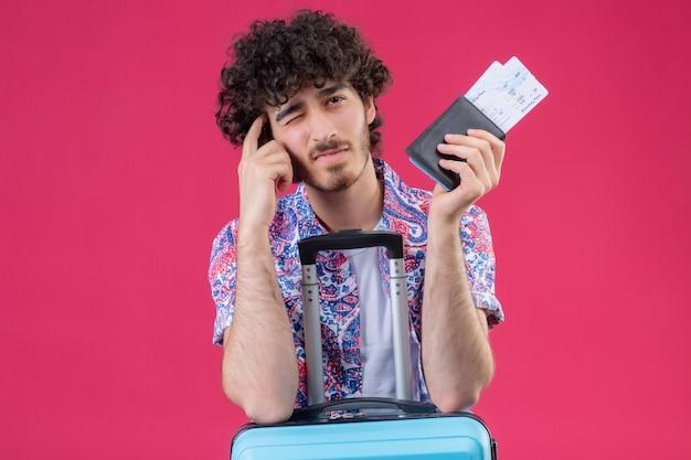 Nachdenklicher junger hübscher lockiger reisender mann, der brieftasche und flugtickets hält, die arme auf koffer und finger auf schläfe setzen, mit einem auge geschlossen auf isolierter rosa wand mit kopienraum