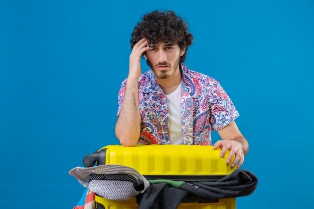 Nachdenklicher junger hübscher lockiger reisender mann, der hände auf kopf und auf koffer voller tücher auf isolierter blauer wand mit kopienraum setzt