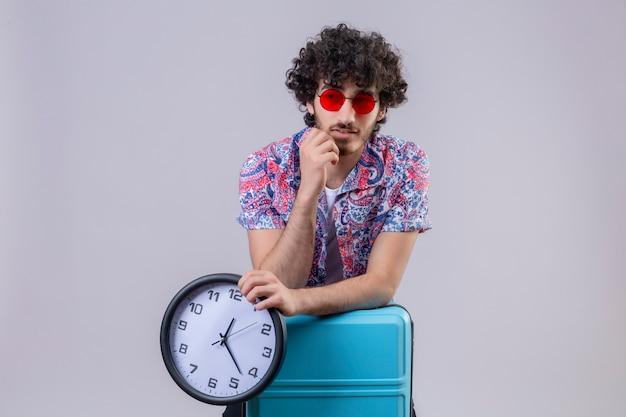 Nachdenklicher junger hübscher lockiger reisender mann, der sonnenbrille trägt und uhr hält und arme auf koffer mit hand auf kinn auf isolierter weißer wand mit kopienraum setzt