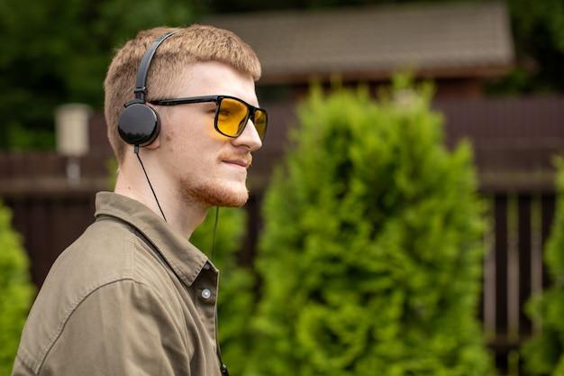 Nachdenklicher junger hübscher mann in den kopfhörern, die draußen stehen, musikpädagogisches podcast-radio hörend, sommergrüne natur. motivation mood playlist, freizeit, harmonie klingt konzept