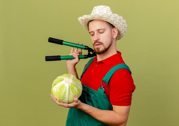 Nachdenklicher junger hübscher slawischer gärtner in der uniform und im hut, die in der profilansicht stehen und kohl und scheren auf der schulter lokalisiert auf olivgrüner wand mit kopienraum halten