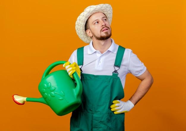 Nachdenklicher junger hübscher slawischer gärtner in uniform und hut, der bewässerung hält, kann hand auf taille halten, die seite betrachtet, die auf orange wand lokalisiert ist