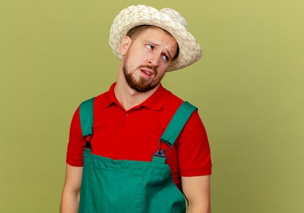 Nachdenklicher junger hübscher slawischer gärtner in uniform und hut, die seite lokalisiert auf olivgrüner wand mit kopienraum betrachten