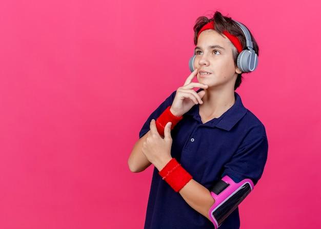 Nachdenklicher junger hübscher sportlicher junge, der stirnband und armbänder und kopfhörer-telefonarmband mit zahnspangen trägt, die gesicht berühren, das oben auf purpurrotem hintergrund mit kopienraum nach oben schaut